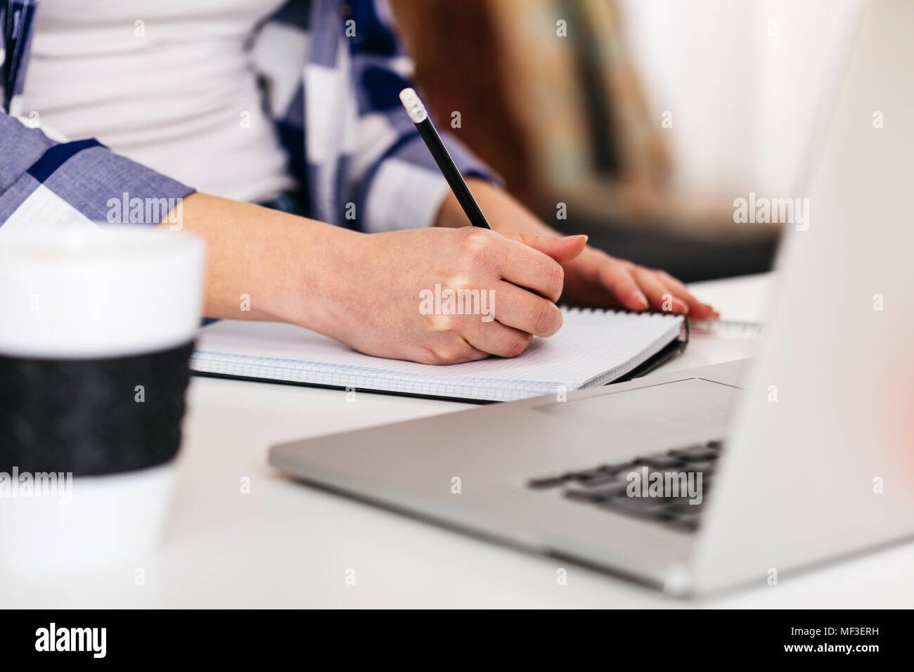 Close-up of woman with laptop taking notes at desk - Stock Image
