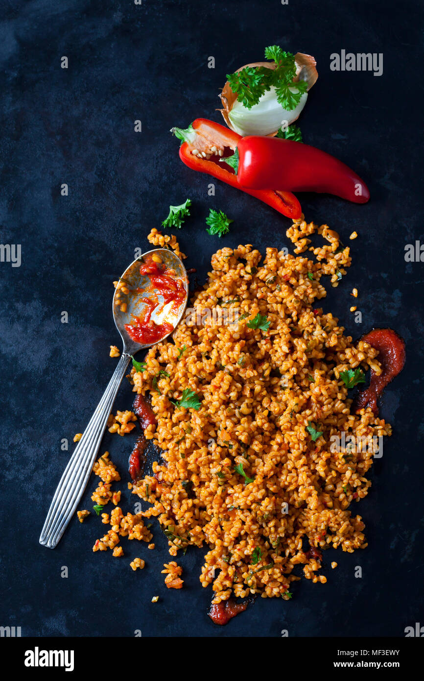 Bulgur wheat salad and ingredients on dark ground - Stock Image