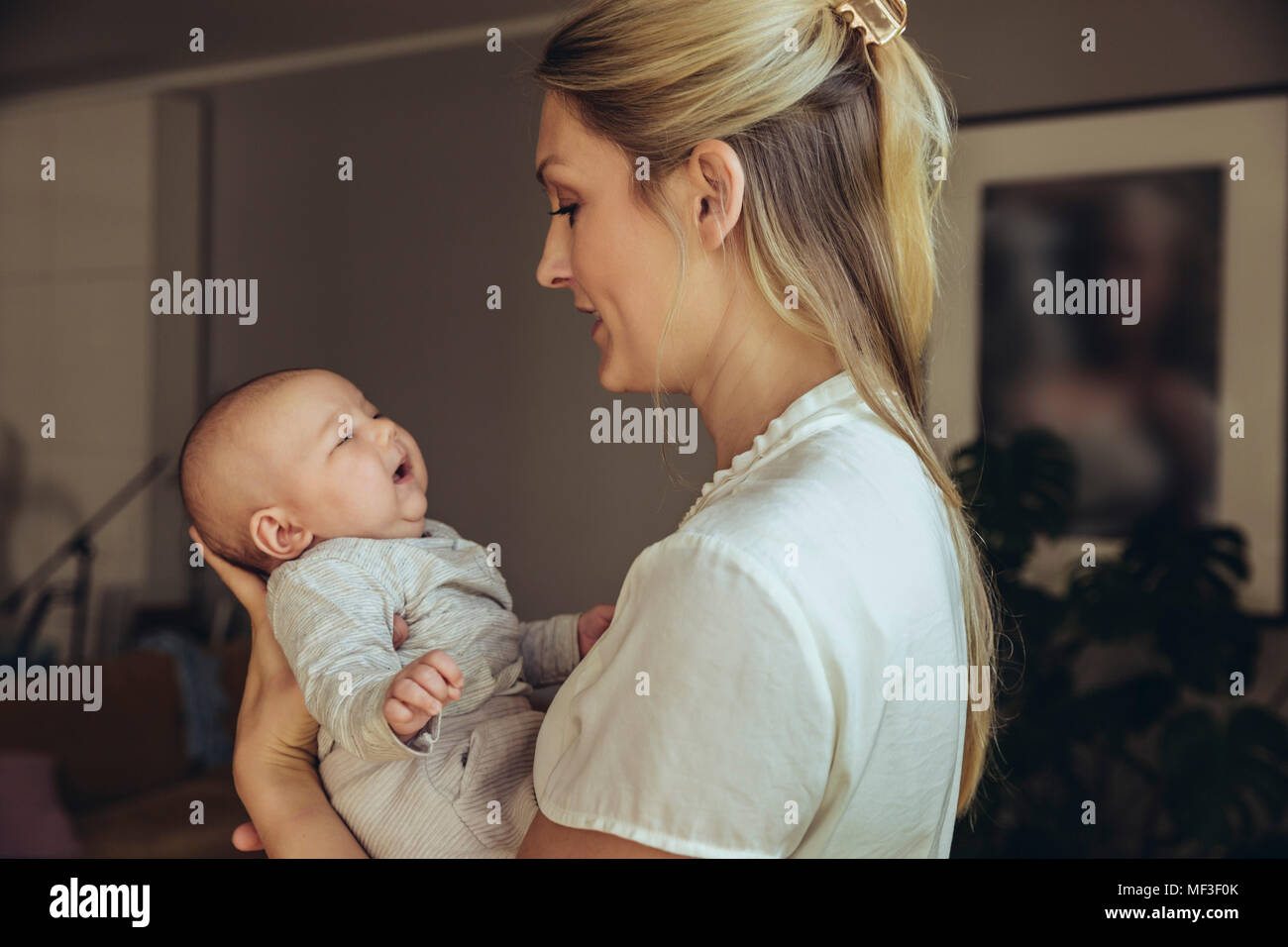 Mother talking to whiny newborn baby Stock Photo