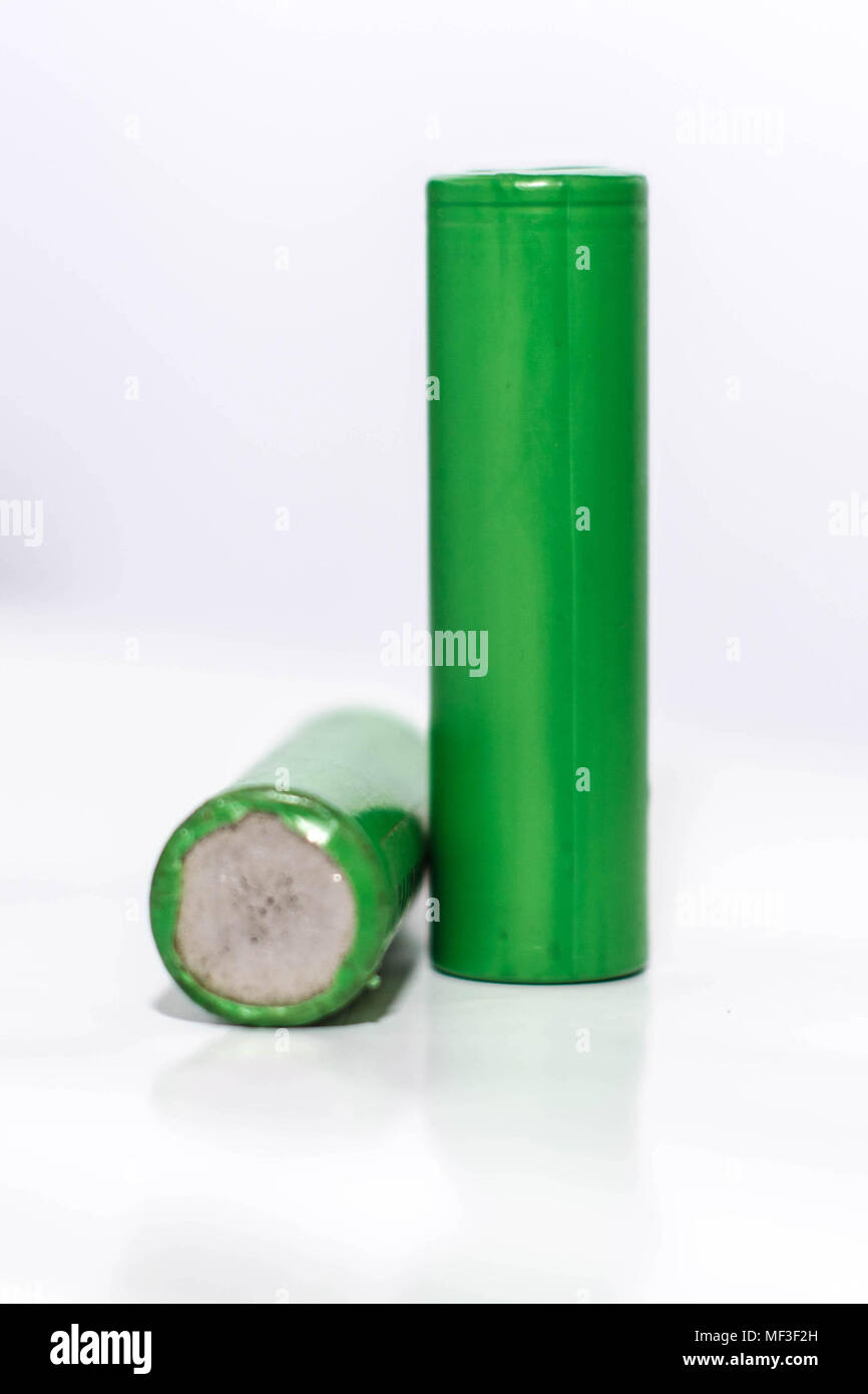 green 18650 battery isolated in white, battery with broken seal - Stock Image
