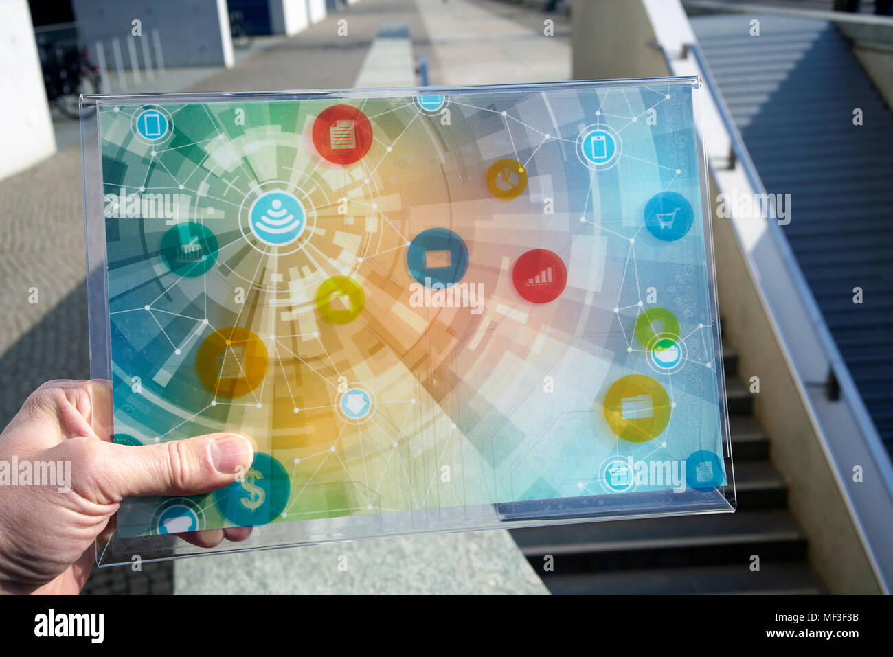 Hand holding futuristic device with digital icons - Stock Image