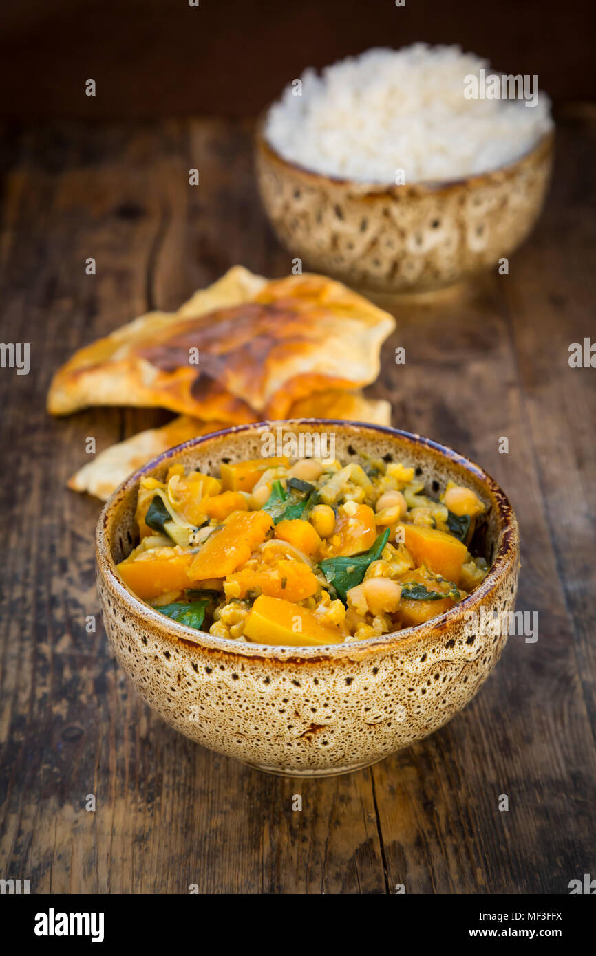 Curry dish with cauliflower, butternut pumpkin, spinach and coriander, papadam and rice - Stock Image