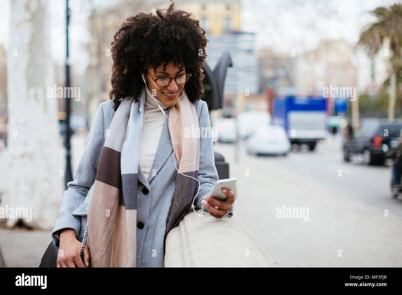 Spain, Barcelona, smiling woman with cell phone and earphones in the city - Stock Image