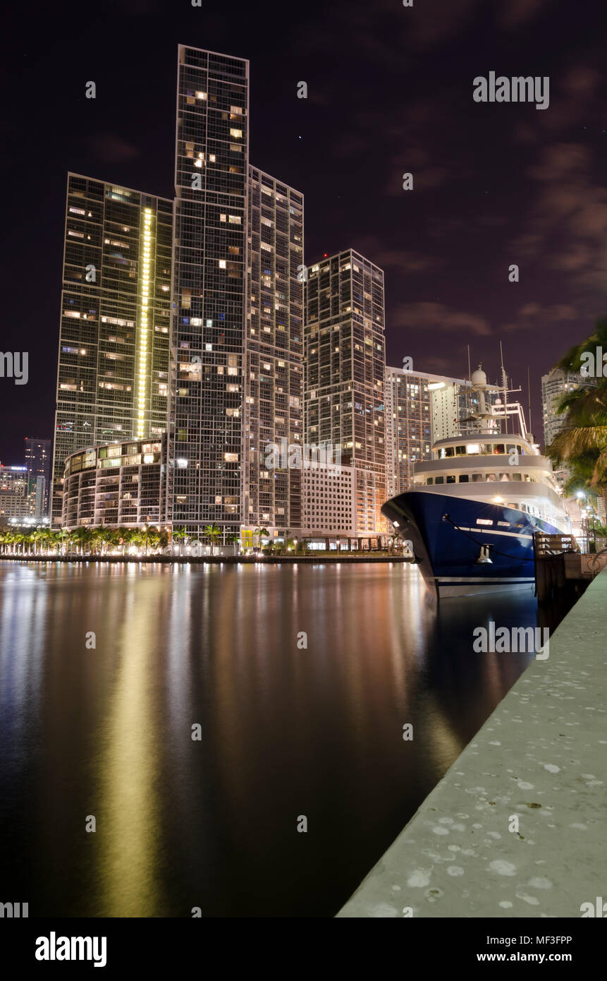 USA, Florida, Miami, High-rise buildings and luxury yacht at night - Stock Image