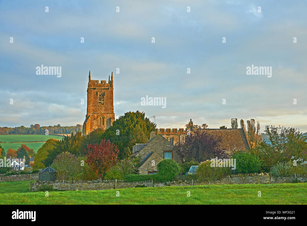 Rural South Warwickshire scene withSt Peter's church in the village of Long Compton with early morning sunshine lighting up the church tower - Stock Image