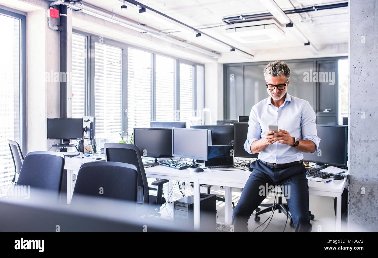 Smiling mature businessman sitting on desk in office using smartphone Stock Photo