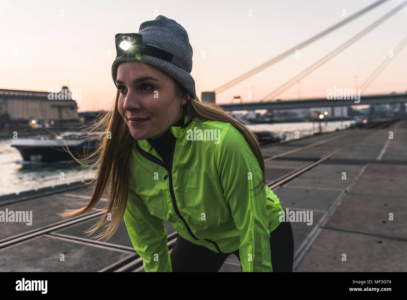 Sportive young woman with headlamp at dusk at the riverside in the city - Stock Image