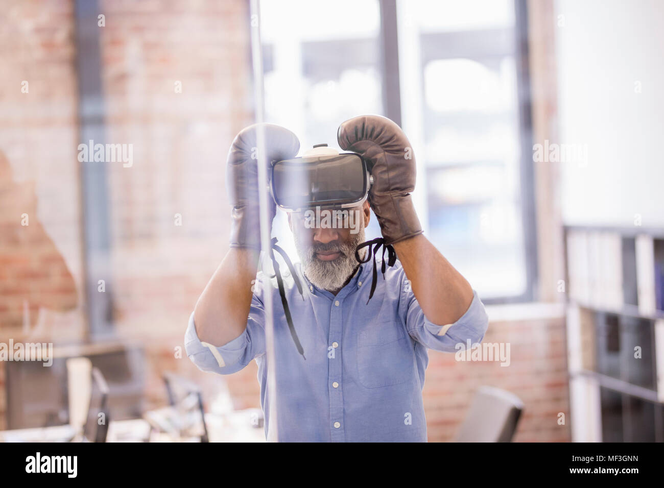 08d065cb469f Portrait of businessman with Virtual Reality Glasses and boxing gloves in  the office