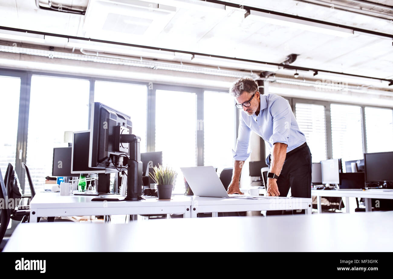 Mature businessman looking at laptop on desk in office - Stock Image