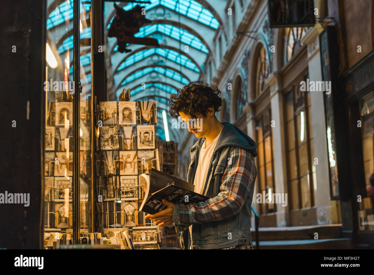 Young man looking at book - Stock Image