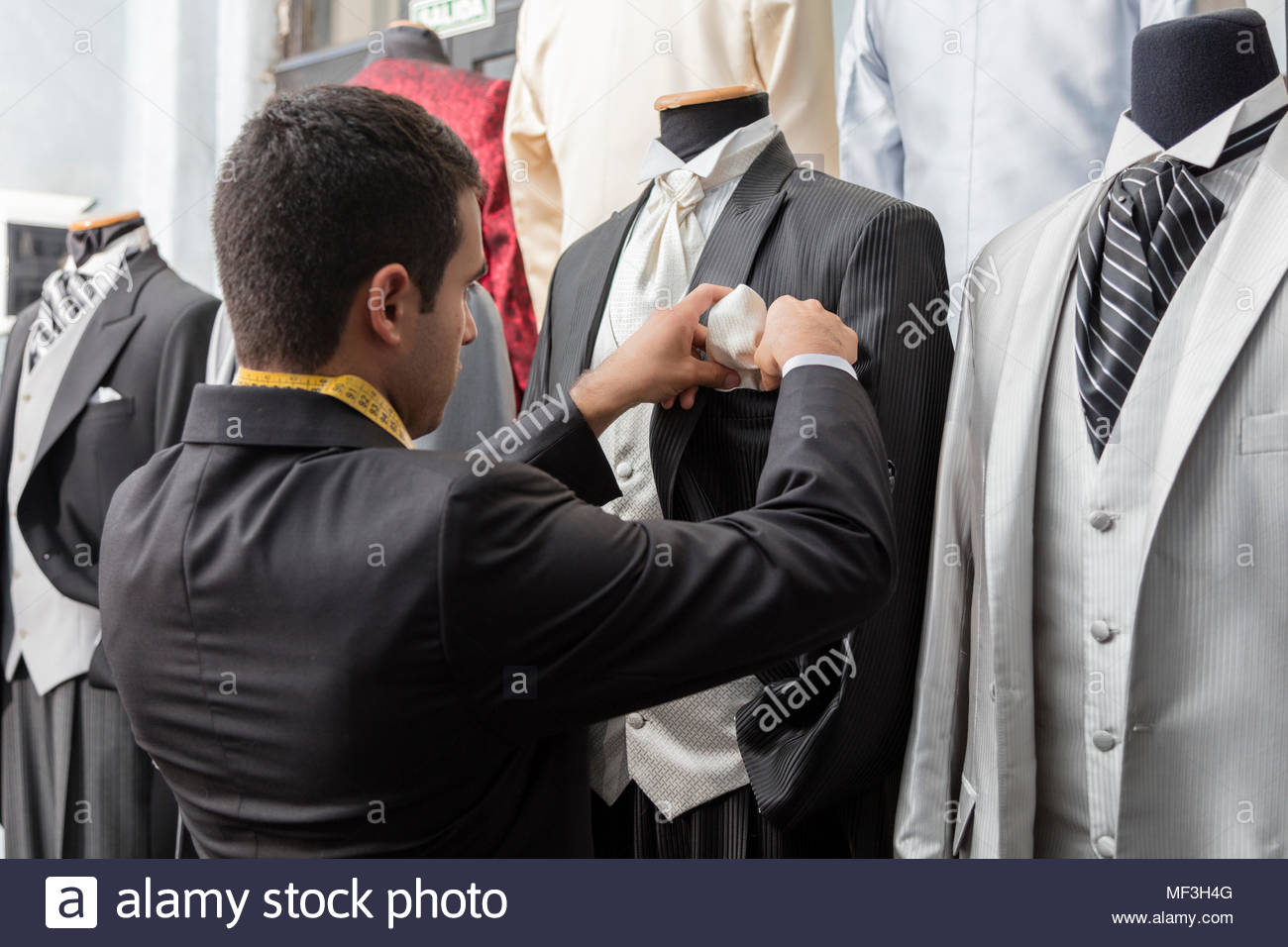 Tailor putting dress handkerchief into tuxedo in tailor shop - Stock Image