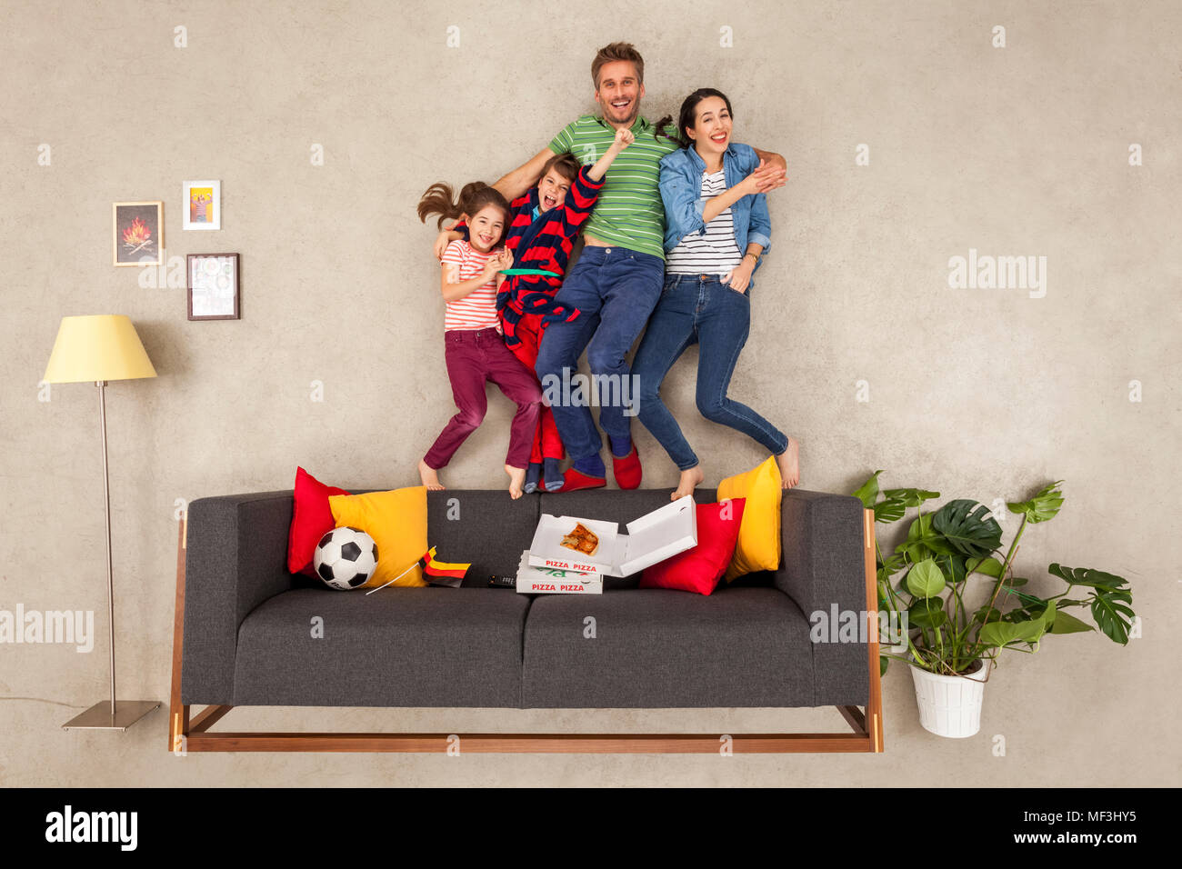 Happy family with two children watching football in living room - Stock Image