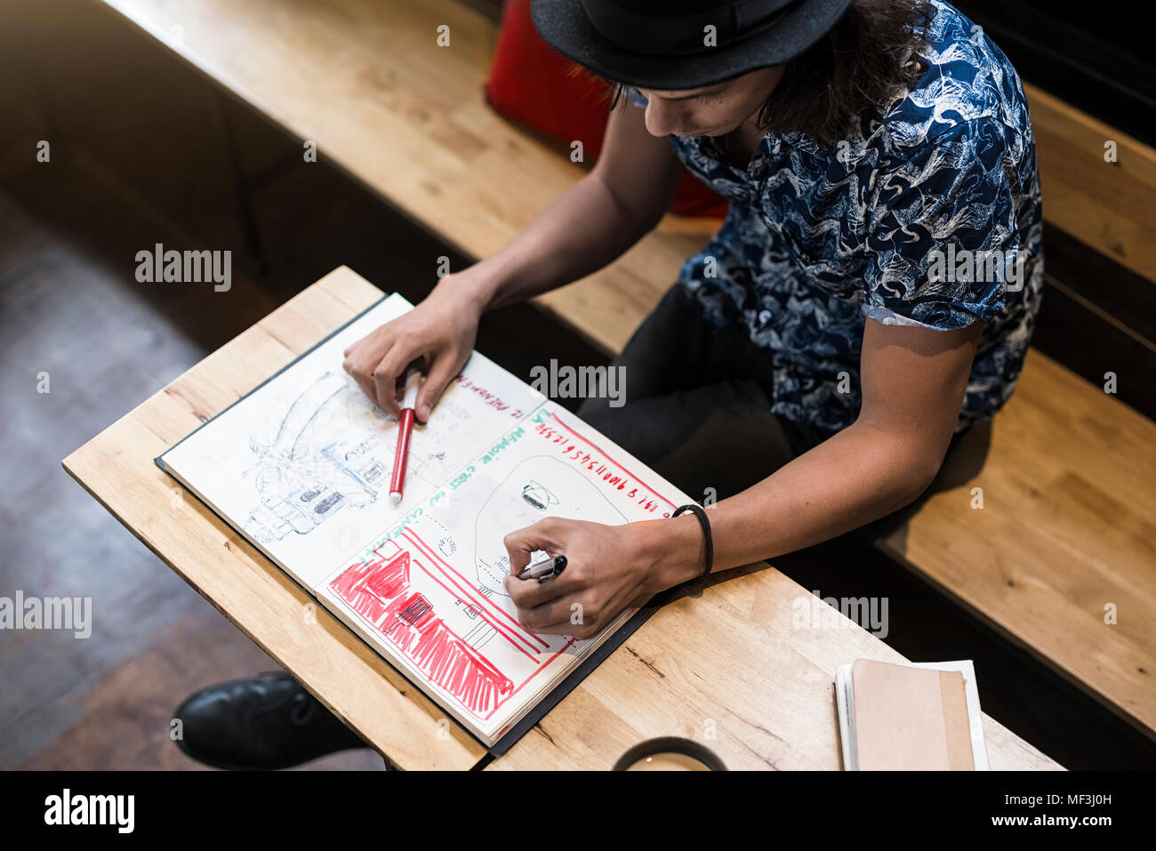 Artist sitting in cafe,  drawing into his notebook - Stock Image