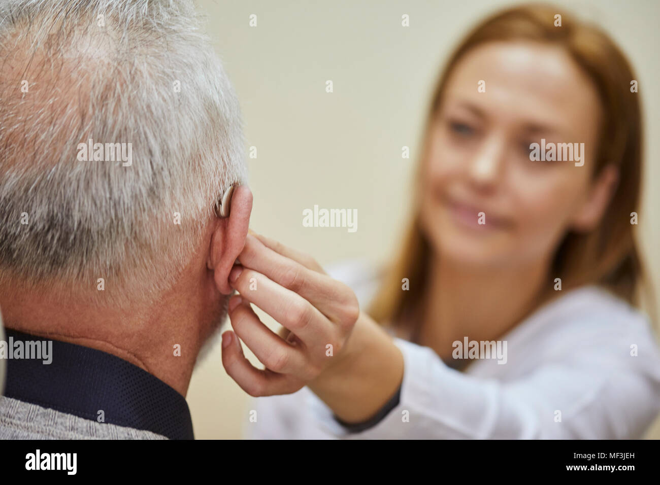 Female doctor applying hearing aid to senior man's ear Stock Photo