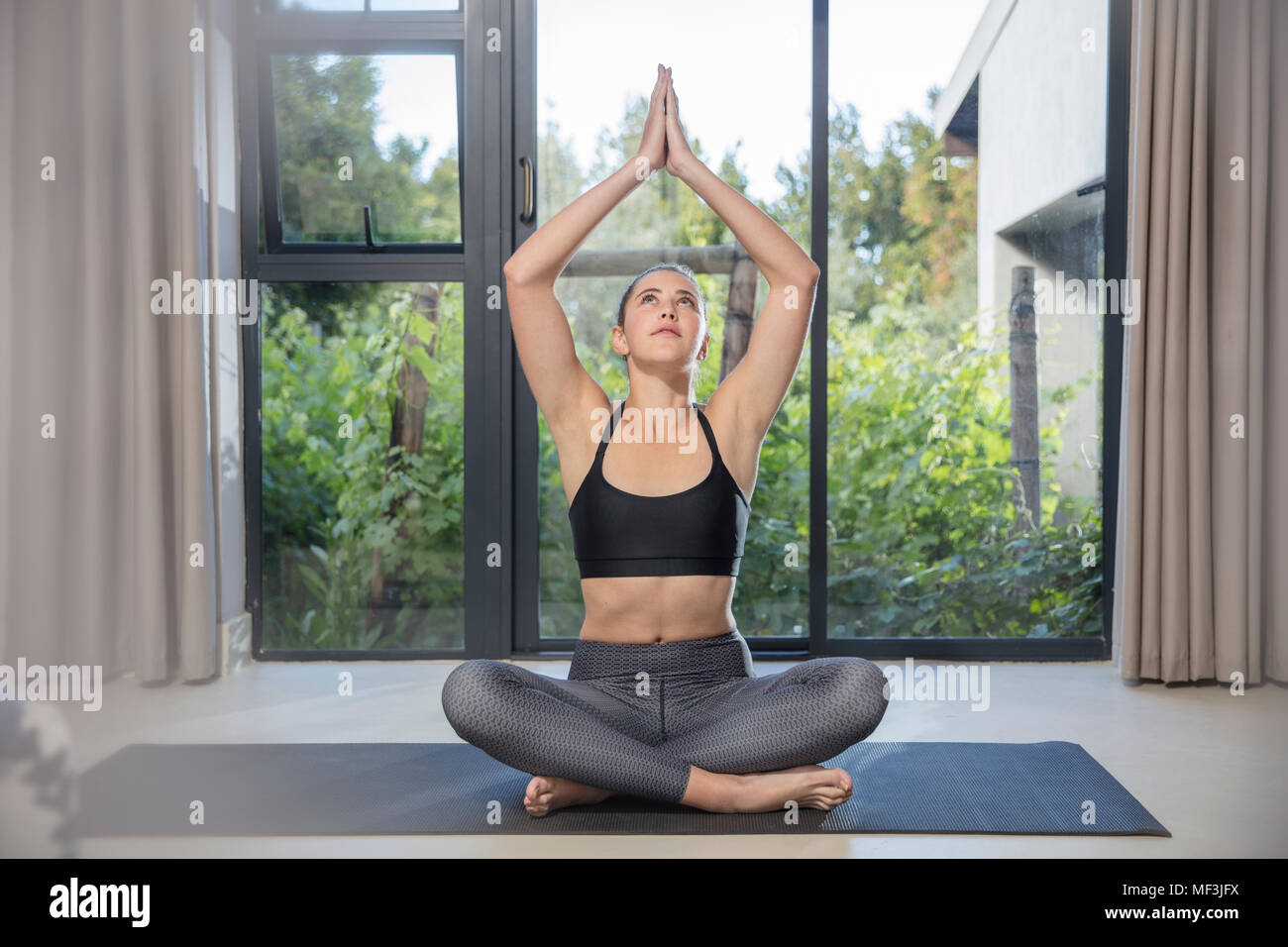 Young woman doing yoga exercise at the window - Stock Image