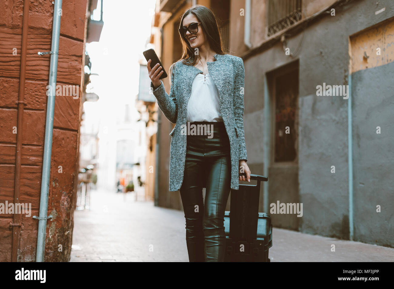 Young businesswoman in the city checking cell phone - Stock Image