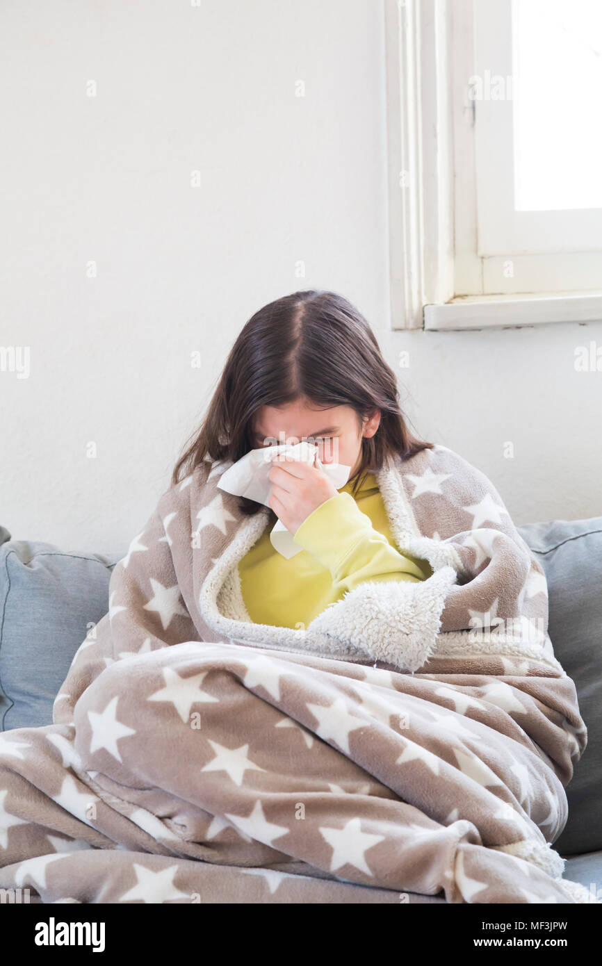 Girl having a cold sitting on the couch at home blowing nose - Stock Image