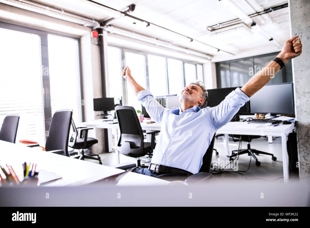 Happy mature businessman sitting at desk in office raising his arms - Stock Image