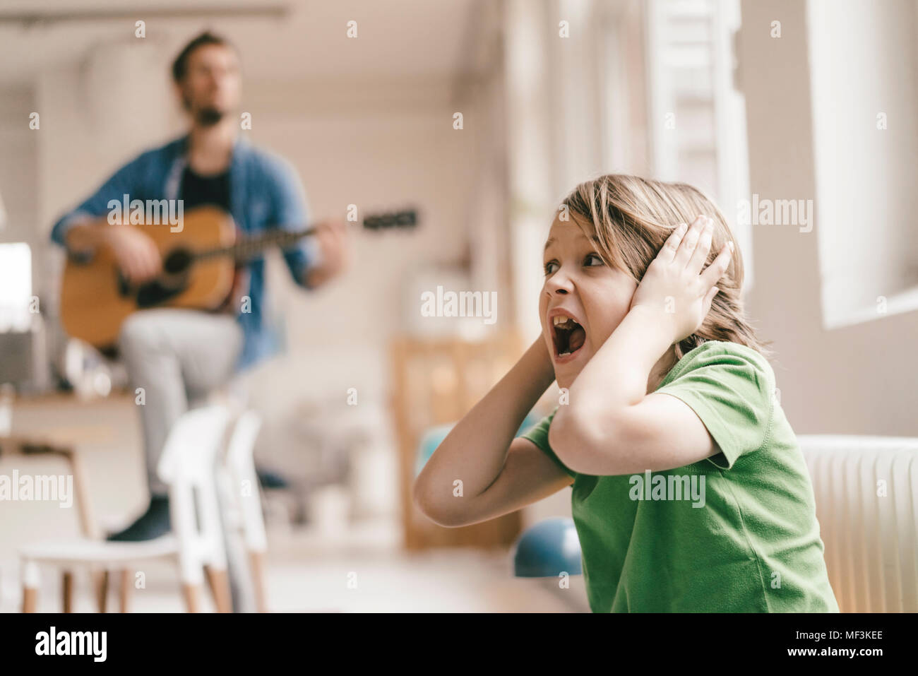 Horrified son covering his ears with father playing guitar at home Stock Photo