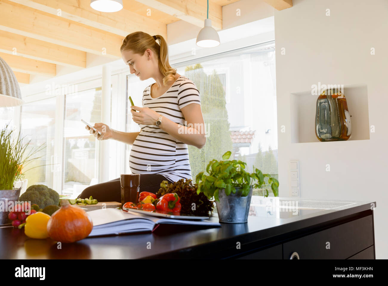 Pregnant woman in kitchen at home using cell phone - Stock Image