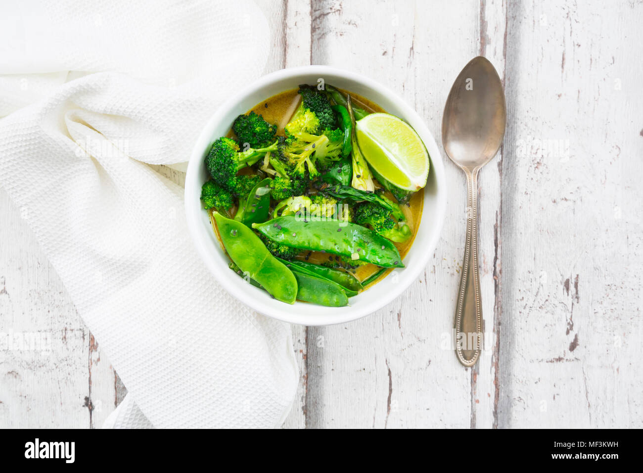 Green thai curry with broccoli, pak choi, snow peas, baby spinach, lime and rice - Stock Image