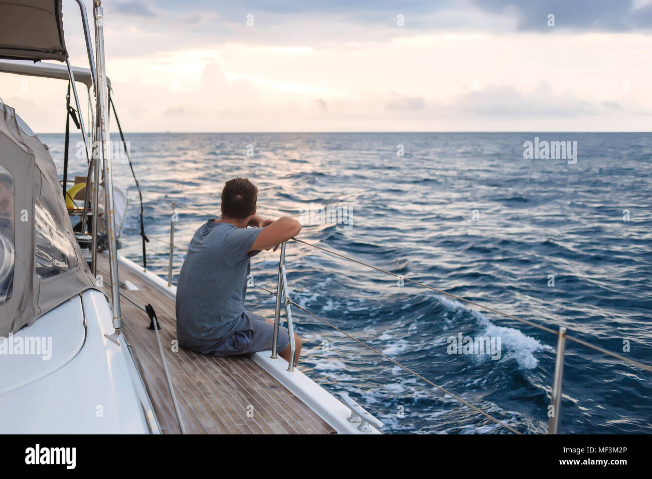 Indonesia, Lombok island, man sitting on deck of a sailing boat - Stock Image