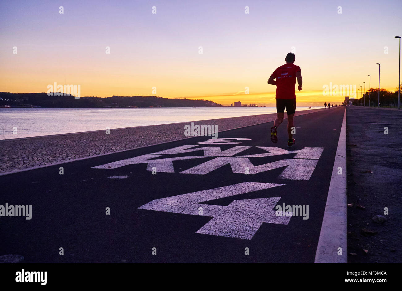 Portugal, Lisbon, Tagus river at sunset, jogger - Stock Image