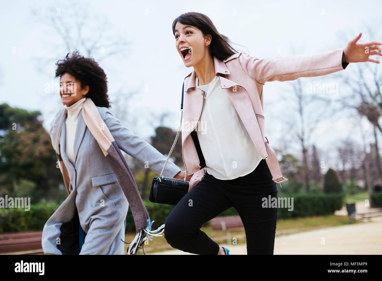 Spain, Barcelona, two exuberant women running in city park - Stock Image
