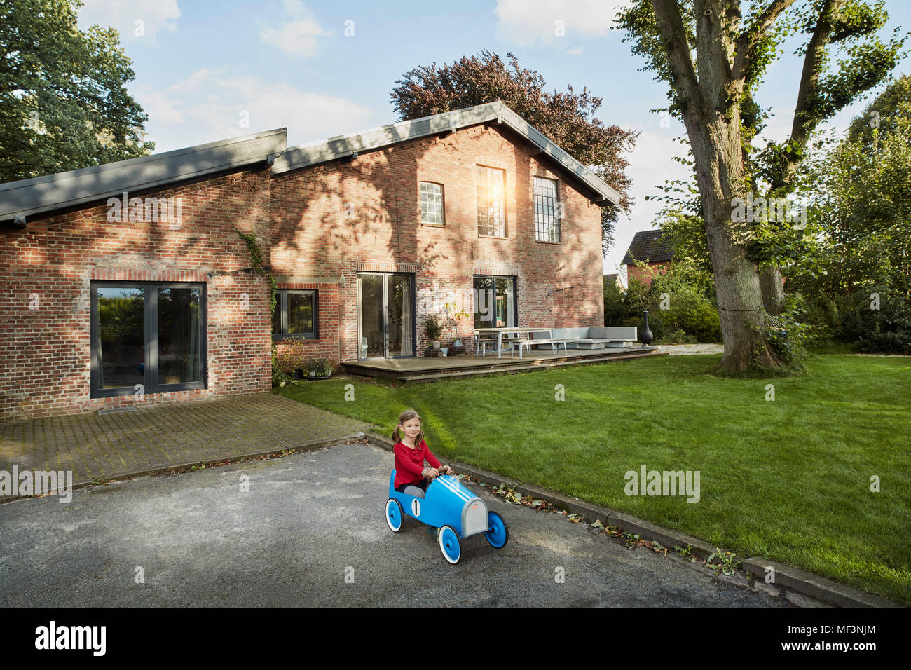 Girl playing with soapbox in driveway of residential house - Stock Image