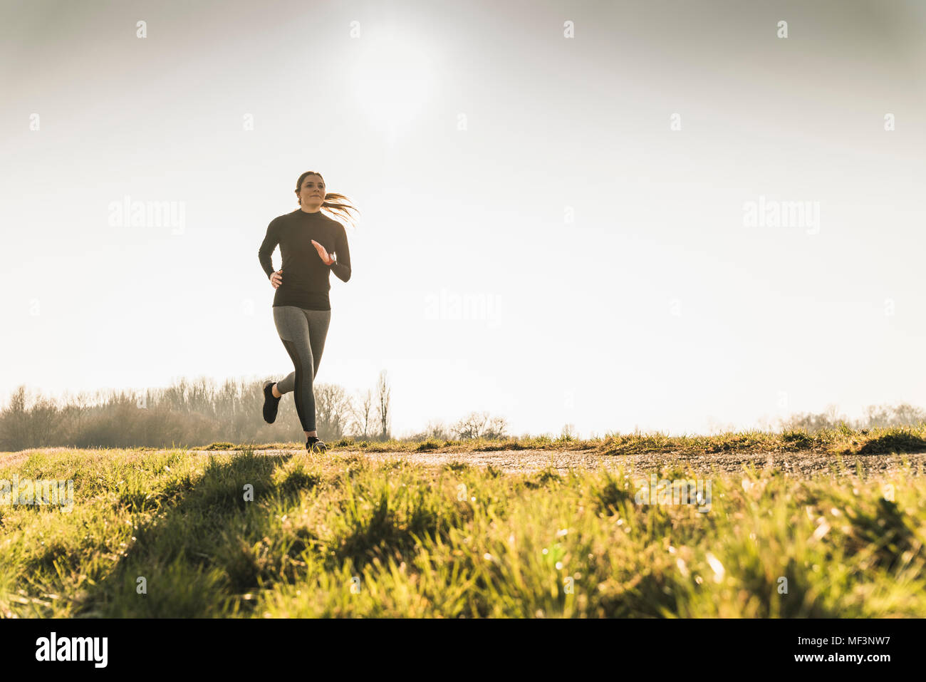 Young woman running on rural path - Stock Image