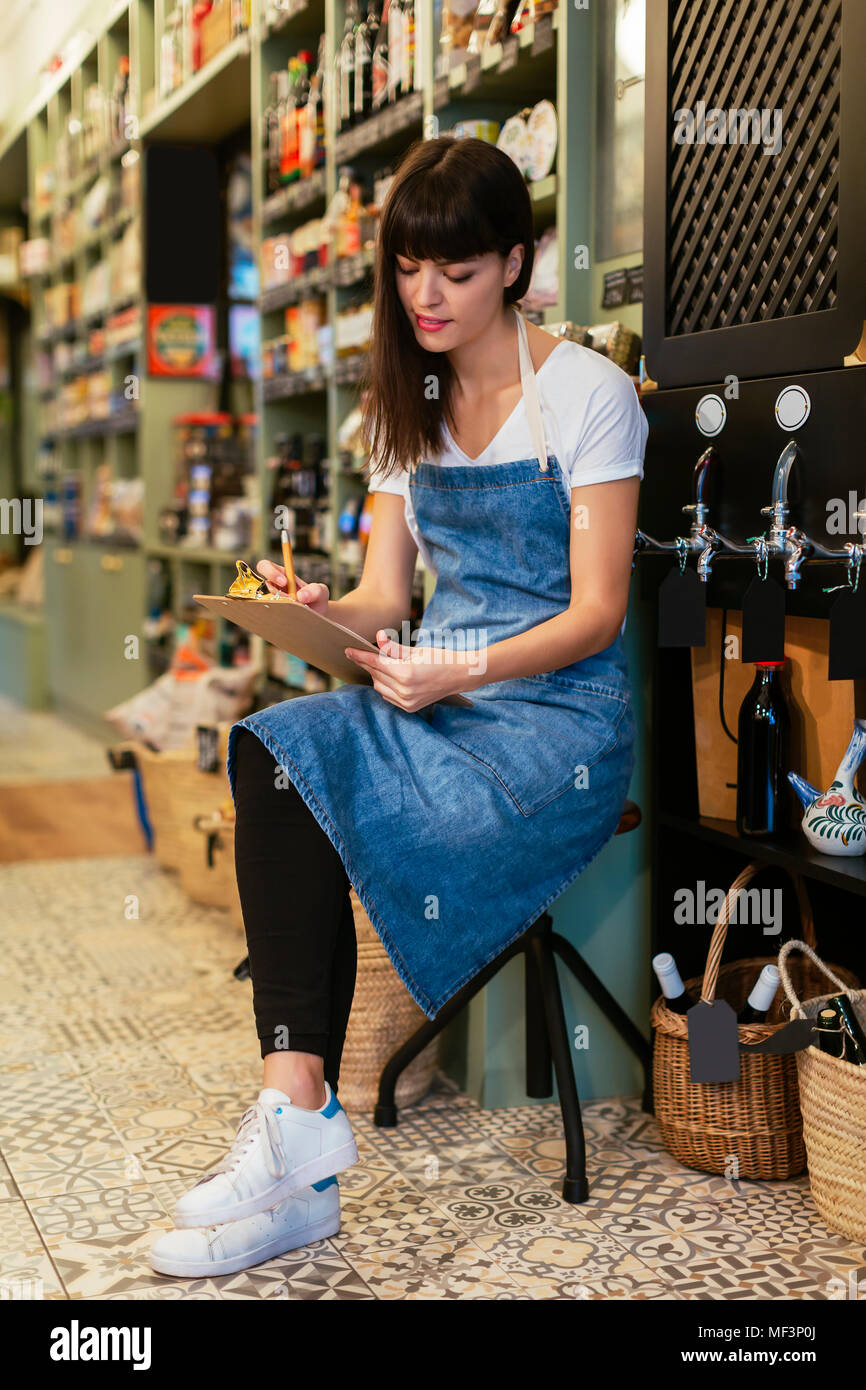 Woman sittting on stool in a store taking notes - Stock Image