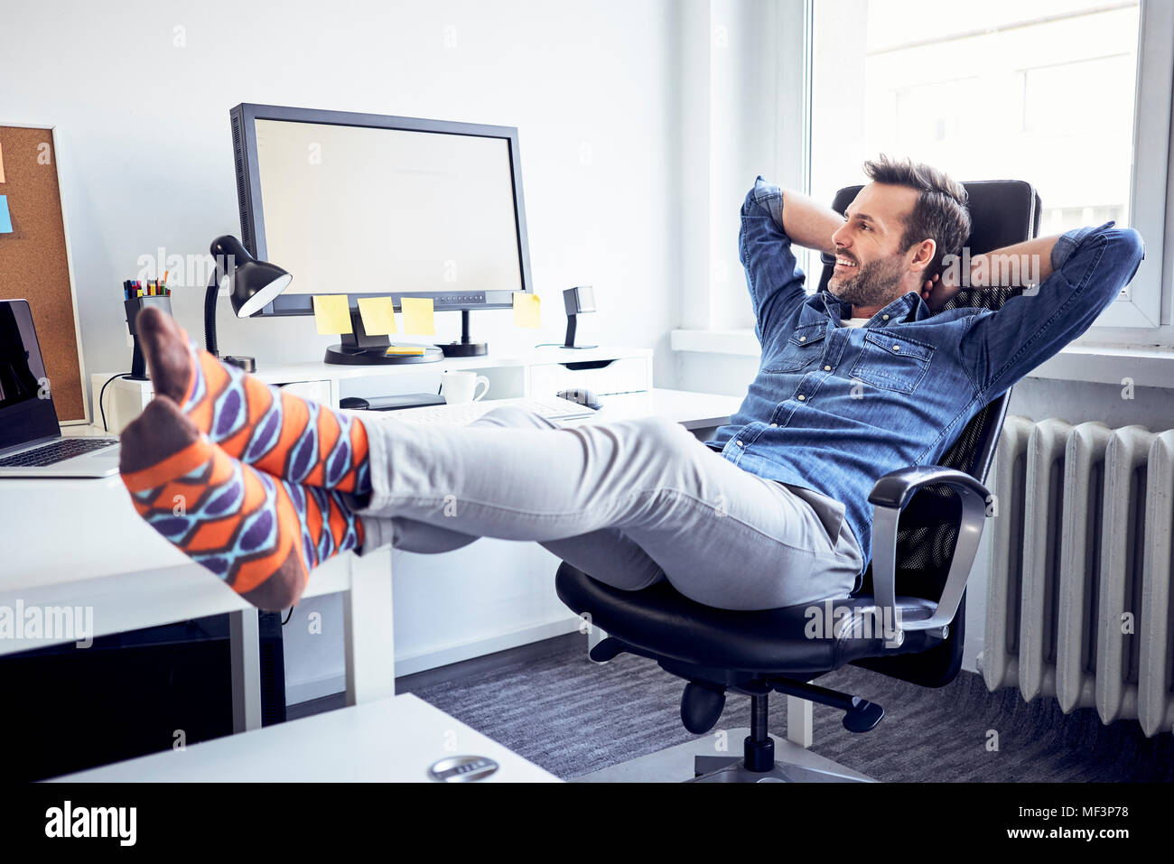 Relaxed man sitting at desk in office looking at computer screen - Stock Image