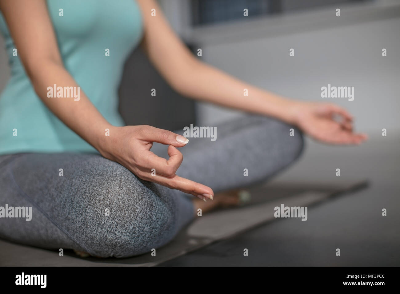 Close-up of woman doing yoga exercise in studio - Stock Image