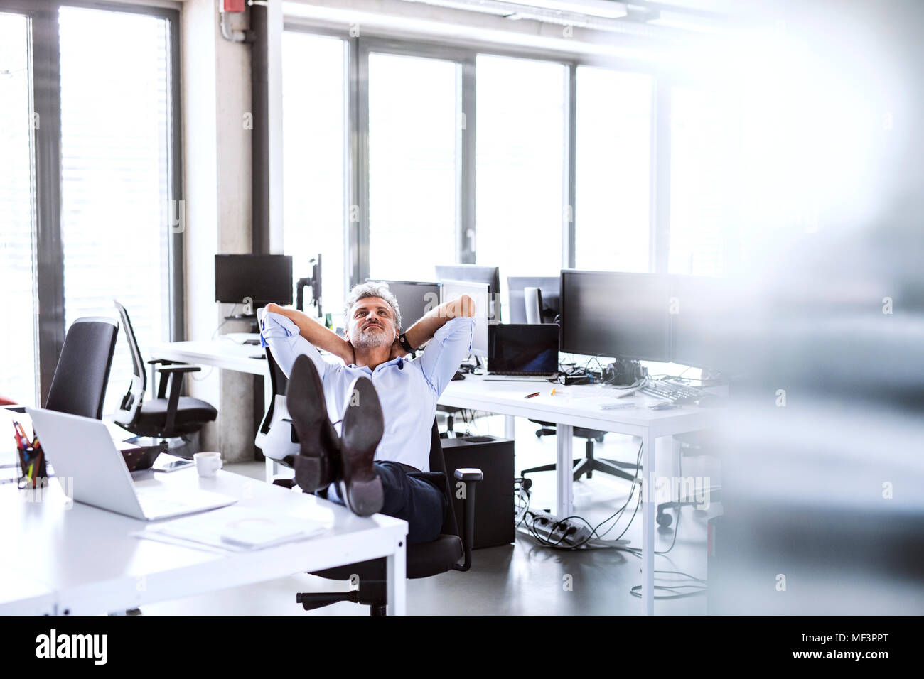 Relaxed mature businessman sitting at desk in office leaning back - Stock Image