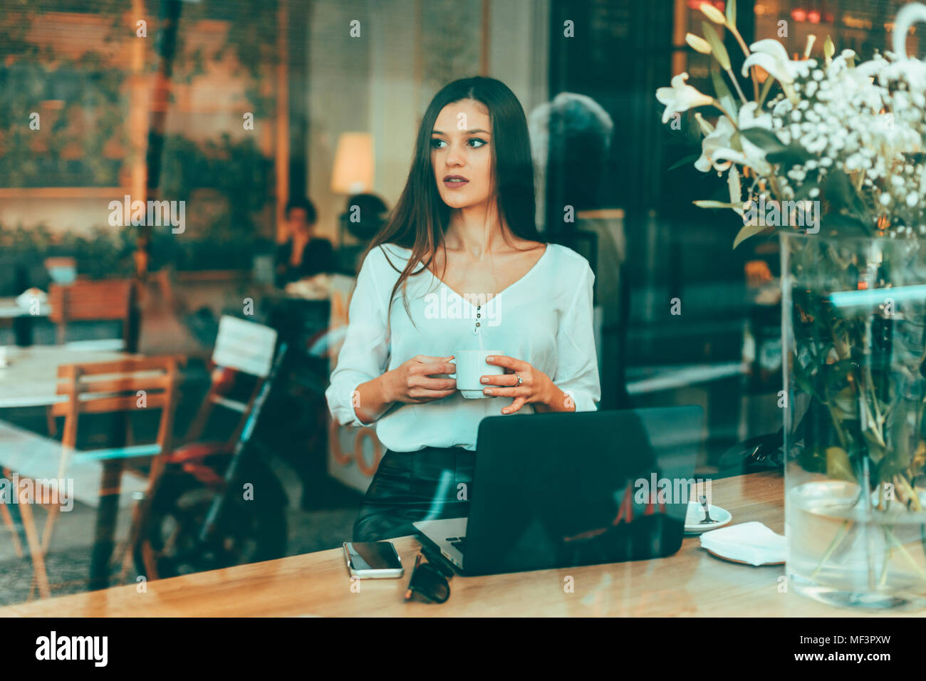 Portrait of young businesswoman waiting in a coffee shop - Stock Image