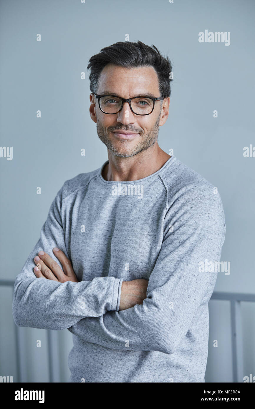 Portrait of smiling man with stubble wearing grey sweatshirt and glasses - Stock Image