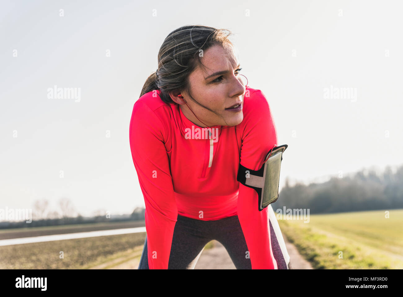 Young woman having a break from running in the countryside - Stock Image