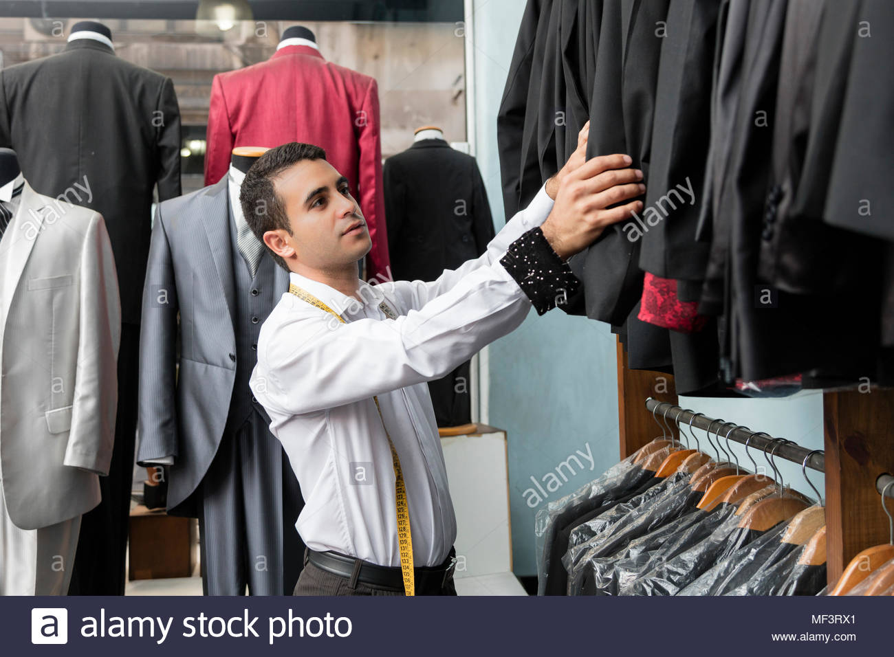 Tailor tidying up suit jackets in tailor shop - Stock Image