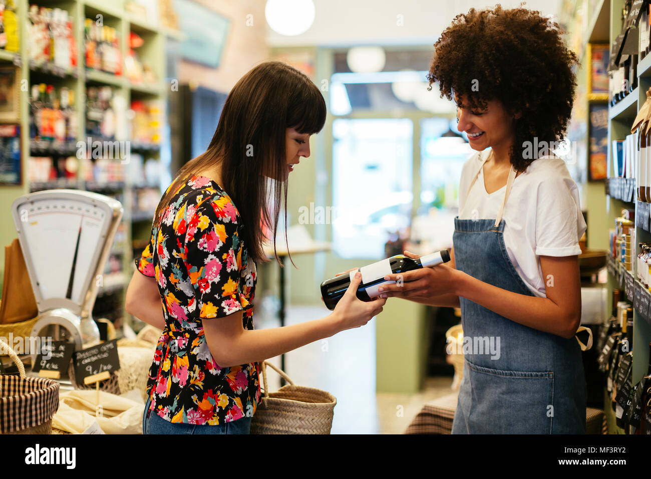 Shop assistant advising customer with wine bottle in a store - Stock Image