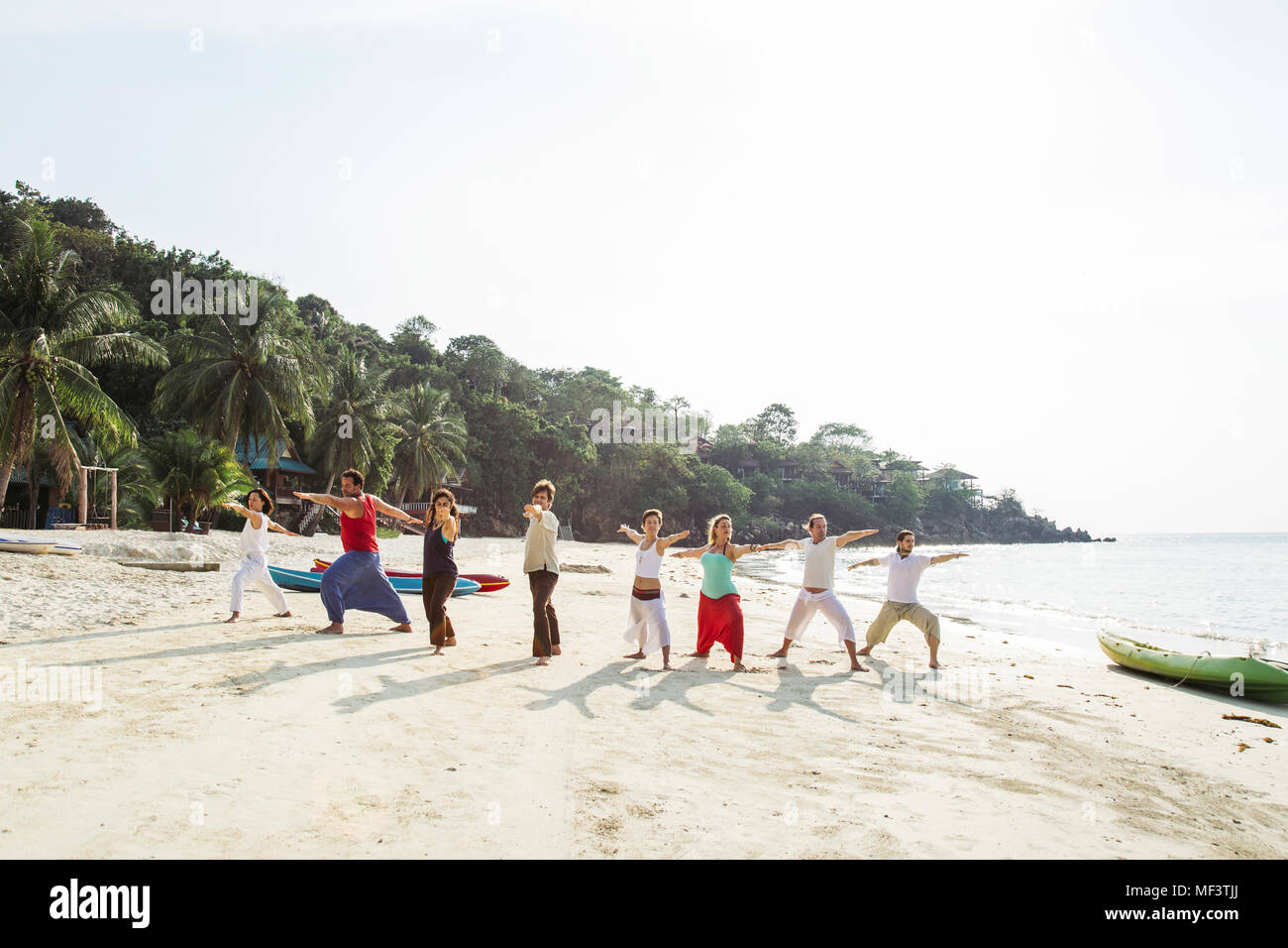 Thailand, Koh Phangan, group of people doing yoga on a beach - Stock Image