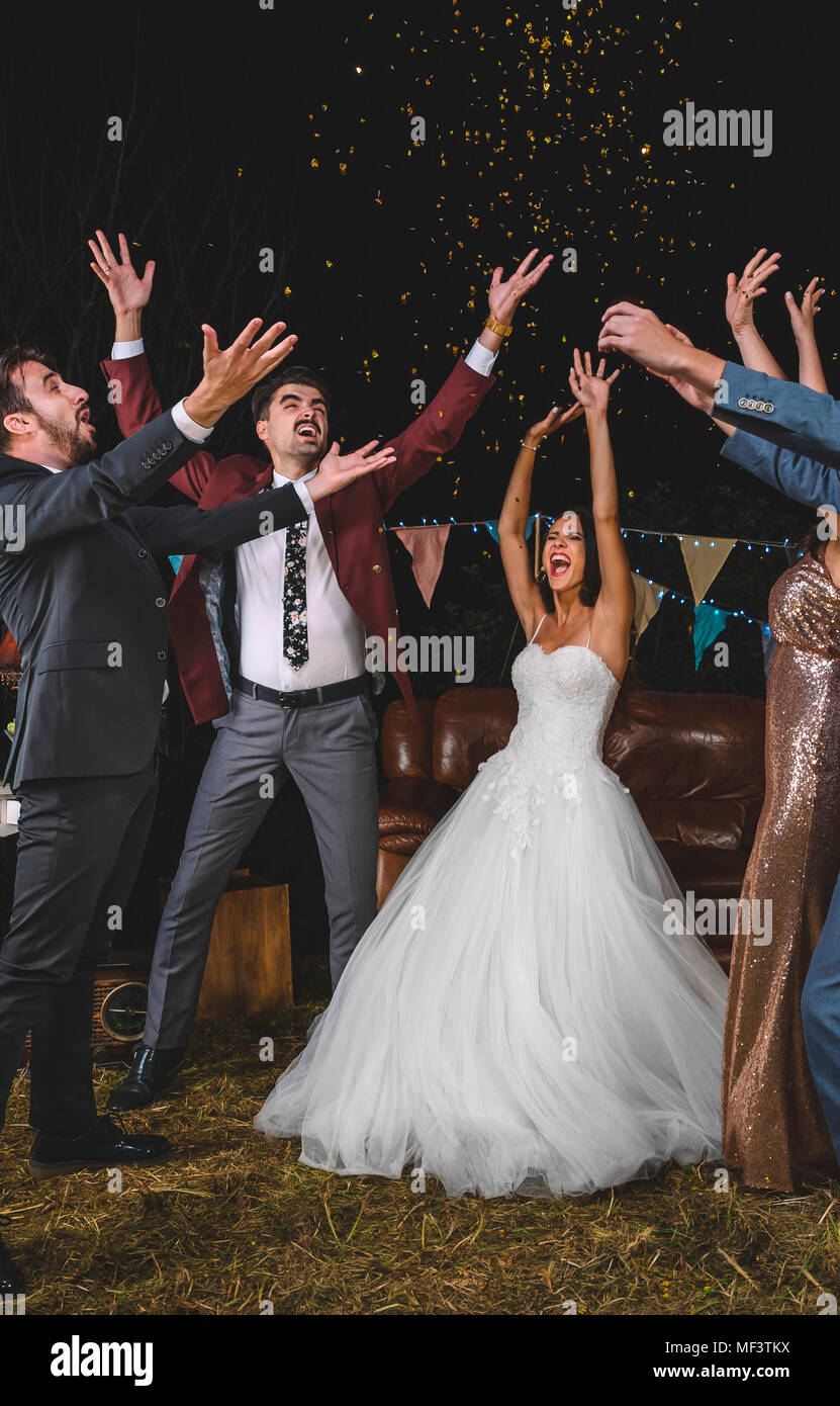 Cheerful wedding couple and friends raising their arms while ...