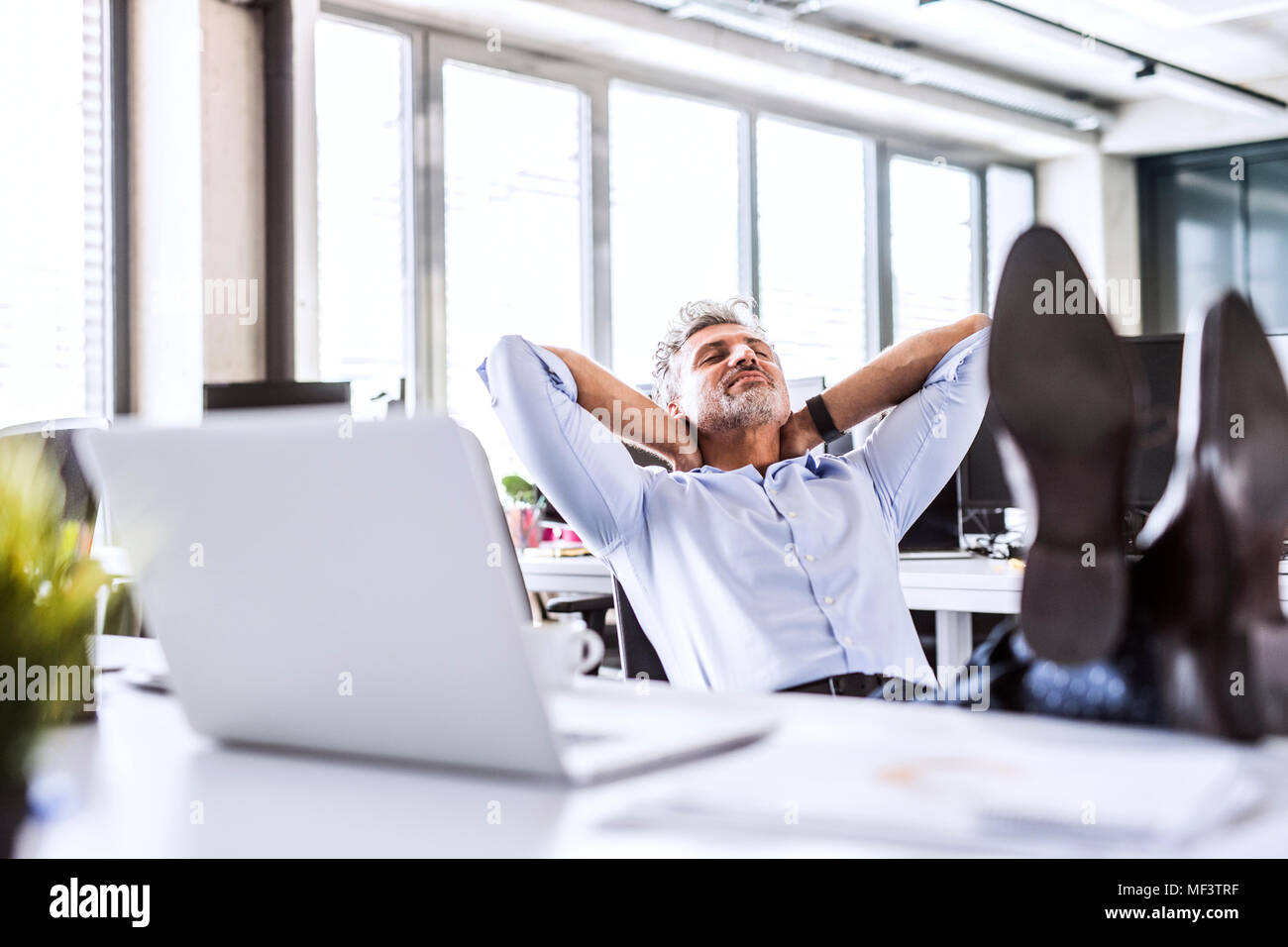 Relaxed mature businessman sitting at desk in office leaning back Stock Photo