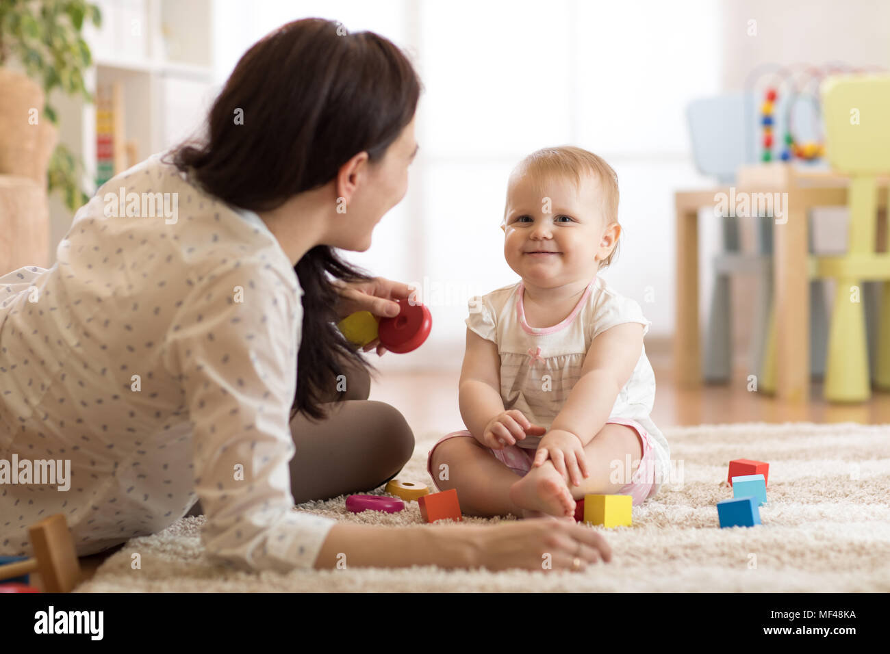 Adorable Baby Girl Playing With Educational Toys In Nursery Child