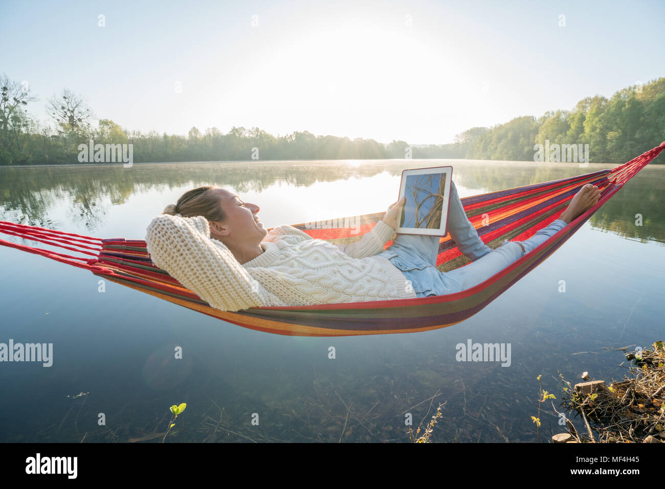 Young woman by the lake hanging on hammock reading on digital tablet one the morning. People relaxation travel technology concept. Shot in France, Eu Stock Photo