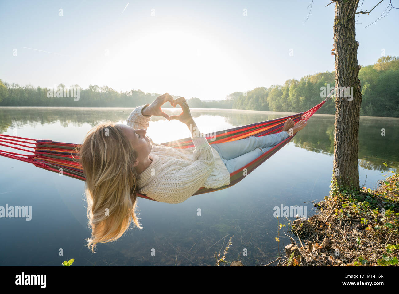 Young woman relaxing on hammock making a heart shape finger frame on beautiful lake landscape, love people romance concept. France, Europe Stock Photo