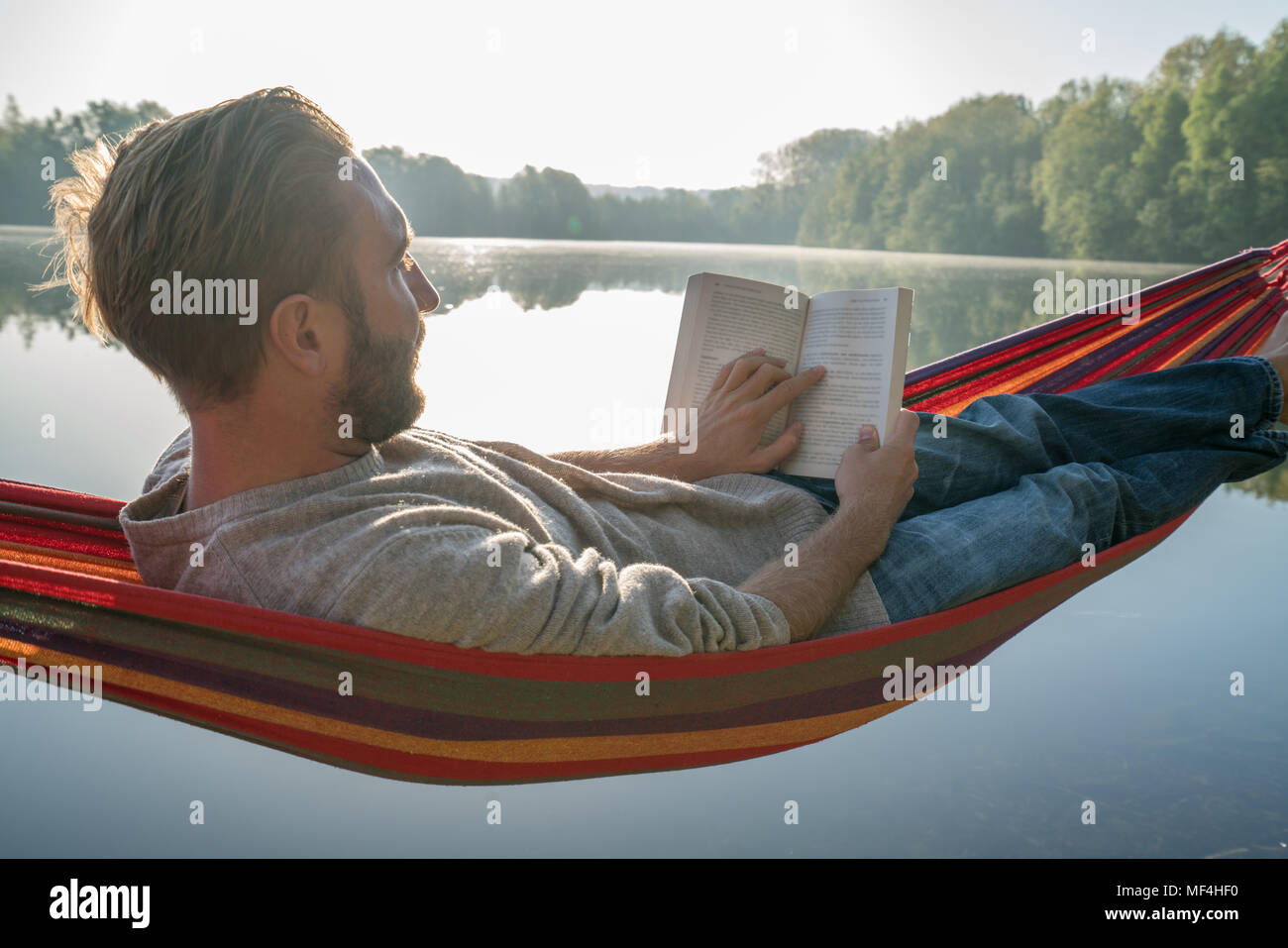 Young man on hammock by the lake in the morning reading a book, beautiful sunlight. People travel learning relaxation concept. Shot in France, Europe Stock Photo