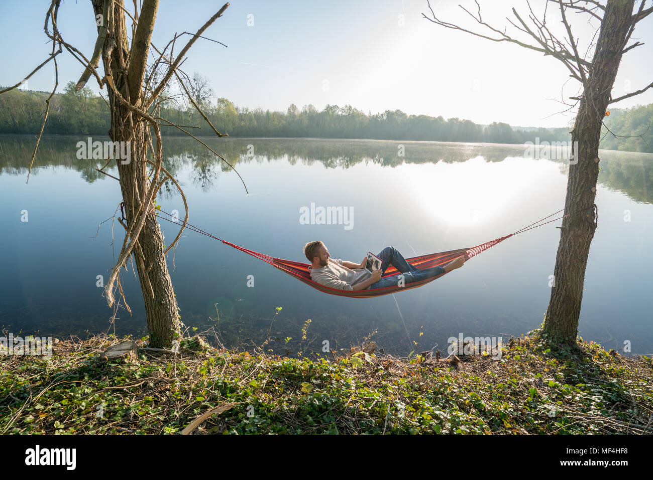 Young man by the lake hanging on hammock reading on digital tablet one the morning. People relaxation travel technology concept. Shot in France, Eu Stock Photo