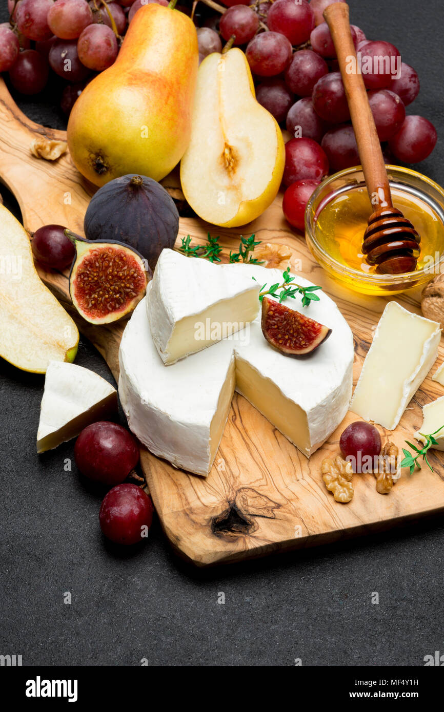 Slice of French brie or camembert cheese and pear on wooden board - Stock Image