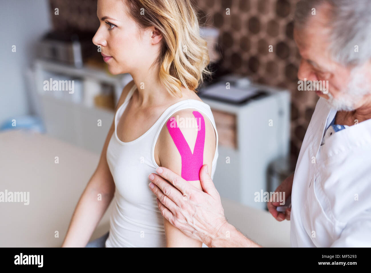 Senior male physiotherapist applying tape on a female patient. - Stock Image