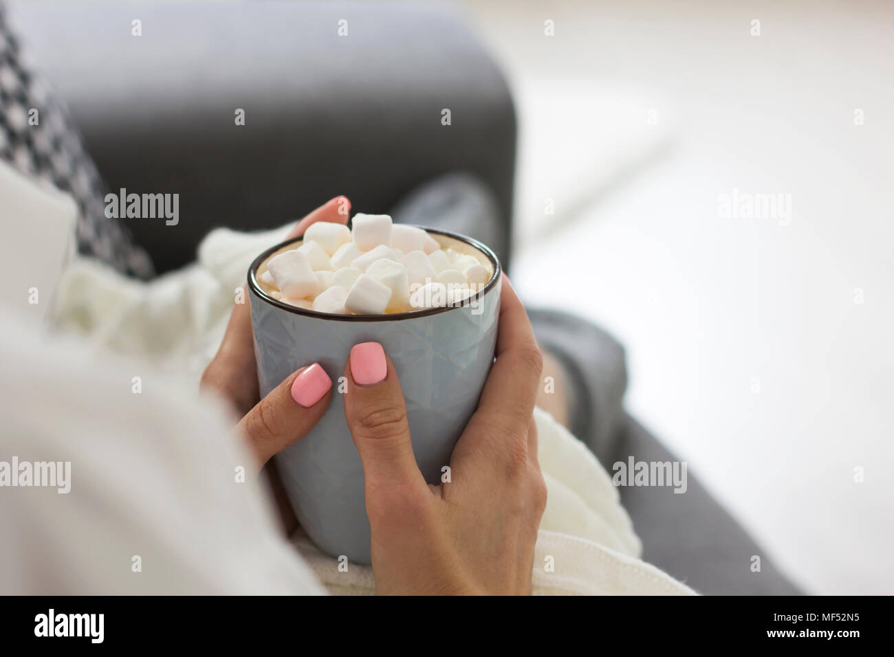 Girl in gray socks sitting on sofa and holding blue Cup of cocoa with marshmallow, cozy home - Stock Image